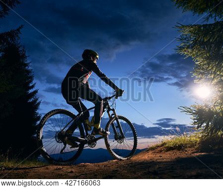 Rear View Of Cyclist Riding Bike Under Blue Evening Sky With Clouds. Silhouette Of Male Bicyclist Ri