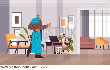 Arab Schoolboy Using Laptop Little Arabic Boy With Mother Doing Homework Education Concept Living Ro