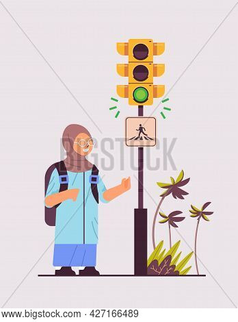 Arab Schoolgirl With Backpack Waiting For Green Traffic Light To Cross Road On Crosswalk Road Safety