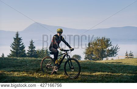 Smiling Man Cyclist In Cycling Suit Riding Bicycle On Grassy Hill. Male Bicyclist In Safety Helmet E