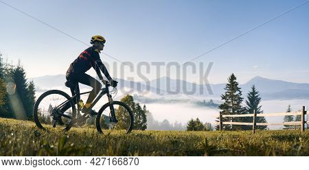 Man Riding Bicycle On Grassy Hill And Looking At Beautiful Misty Mountains. Male Bicyclist Enjoying