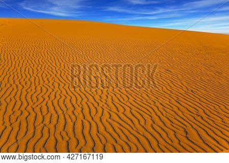 Mesquite Flat Sand Dunes, California. USA. Light sand waves from the desert wind. Orange sunset in the desert. Magic play of light on the sand. Concept of active, ecological and photo tourism