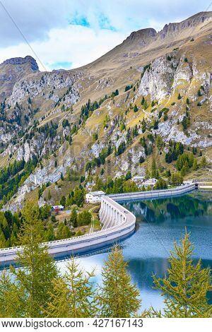 The grand dam raises the water level in the lake. Lago di Fedaya. Magnificent lake at the foot of Mount Marmolada. Italy, Dolomites, Fedaya pass. Travel to the land of lakes and mountains