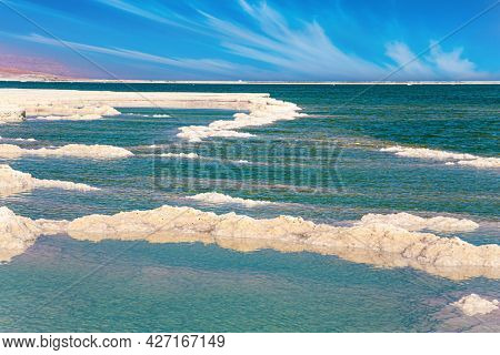Israeli coast of the Dead Sea. The evaporated salt forms intricate patterns. Cirrus clouds fly in the blue sky. Windy spring day