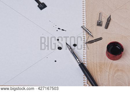 There Is Drawing Paper On A Plywood Board. A Nib Pen And Interchangeable Nibs Lie Side By Side. Blot