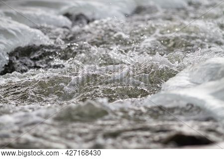 A Fast River Stream Flows Among The Ice. Its Surface Is Covered With Foam And Splashes. Selective Fo