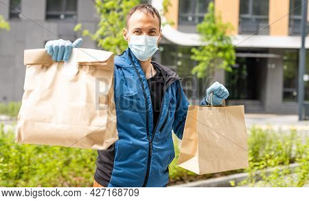 Hispanic Young Delivery Man Wearing Face Mask While Carrying Parcel Box During Coronavirus Outbreak.