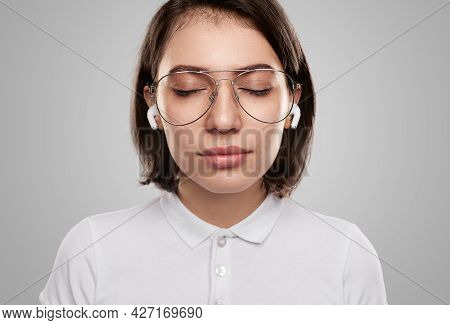 Calm Young Female With Eyes Closed In Eyeglasses And Tws Earbuds Relaxing While Listening To Good Mu