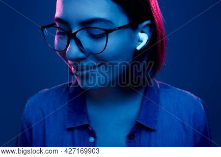 Positive Young Female In Trendy Eyeglasses And True Wireless Earbuds Smiling While Enjoying Good Mus