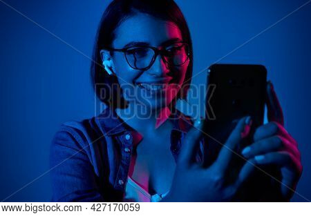 Smiling Modern Young Female In True Wireless Earbuds Using Mobile Phone During Video Call In Studio