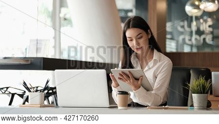 Beautiful Asian Business Woman Using Tablet And Laptop While Working In The Office