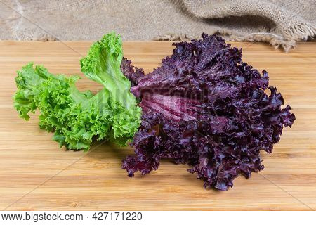 Lettuce Leaves Two Varieties - Red Lollo Rosso And Pale Green Lollo Bionda On A Wooden Surface