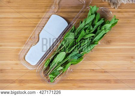 Fresh Spearmint Stems In An Open Transparent Plastic Container On A Wooden Surface, Top View