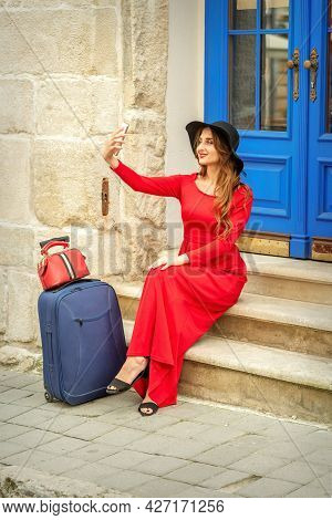 Tourist Young Caucasian Woman In A Red Long Dress And Black Hat With Suitcase Takes A Selfie Sitting