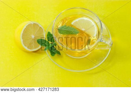 Glass Cup Of The Tea With Mint Leaf And Lemon Slice On The Glass Saucer, Twig Of Fresh Mint And Half