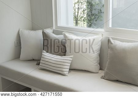 Grey, White And Blue Pillow On Sofa Nook By The Window Of Modern Home.