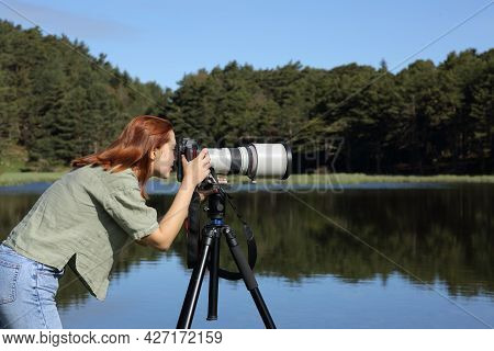 Side View Portrait Of A Photographer Taking Photo With Telephoto And Dslr Camera In A Lake