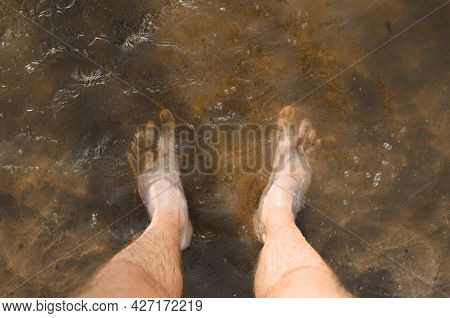 Top View Of A Man Standing Barefoot In Muddy Water, Close-up Of Male Bare Feet In Sand And Mud. Mudd