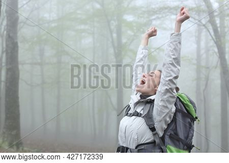 Excited Trekker Celebrating Achievement In A Foggy Forest On Vacation