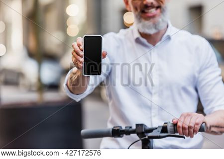 Cropped View Of Happy Middle Aged Man Holding Cellphone With Blank Screen And Standing Near E-scoote