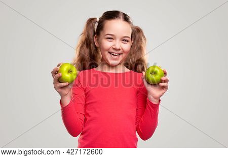 Optimistic Kid With Pigtails Looking And Camera With Smile And Demonstrating Ripe Apples As Symbol O