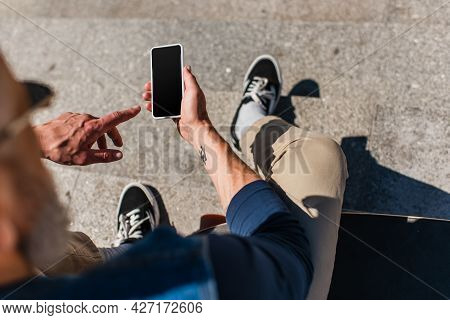 Top View Of Tattooed Mature Man Pointing At Smartphone With Blank Screen Near Longboard