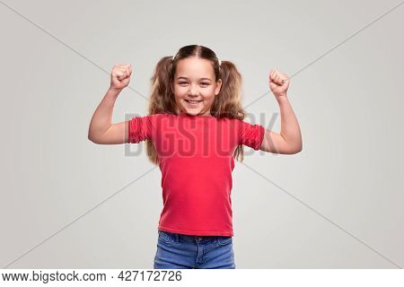 Delighted Strong Girl In Casual Clothes Smiling For Camera And Showing Muscles While Representing He