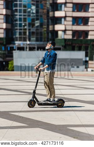 Full Length Of Happy Man In Sunglasses And Helmet Riding E-scooter In Urban City