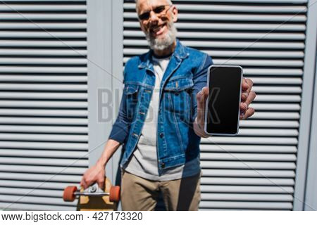 Blurred And Pleased Middle Aged Man In Sunglasses Holding Smartphone With Blank Screen And Longboard