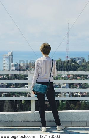 Young Woman Tourist In Full Growth Stands On Observation Deck And Looks At City, Sea And Sky, Back V