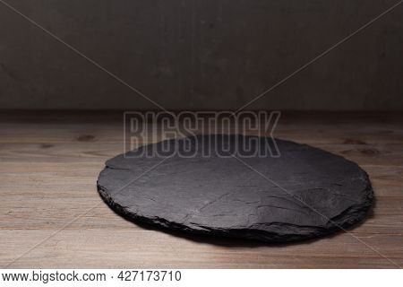 Slate pizza cutting board for homemade bread cooking or baking on table. Empty pizza board at wooden tabletop background. Bakery concept in kitchen
