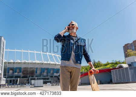 Happy Middle Aged Man In Sunglasses Holding Longboard While Speaking On Cellphone On Urban Street