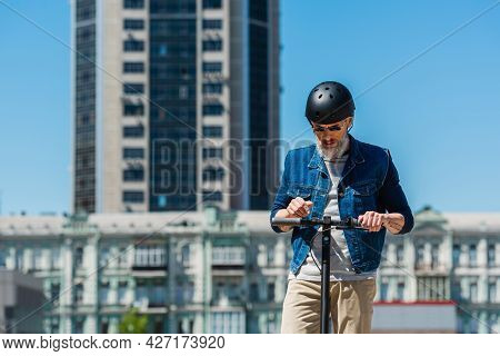 Middle Aged Man In Sunglasses And Helmet Riding E-scooter In Urban City