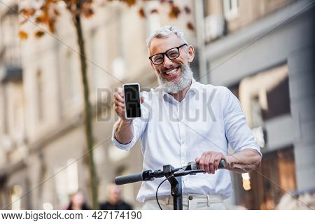 Happy Middle Aged Man In Glasses Holding Cellphone With Blank Screen And Standing Near E-scooter