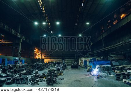 Metallurgical Factory Workshop Interior With Working Welder And Metal Products Ready For Processing,