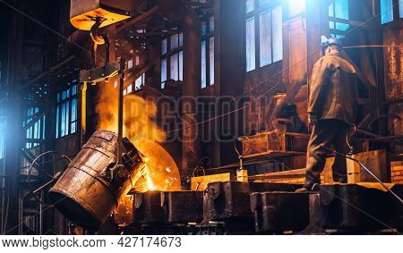 Liquid Metal Pouring Into Molds. Metal Melting In Furnaces In Foundry Metallurgical Plant, Heavy Ind