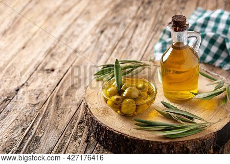 Virgin Olive With Green Olives In Crystal Bowl On Wooden Table. Copy Space