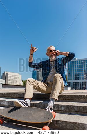 Excited Middle Aged Man In Sunglasses Sitting On Stairs Near Longboard While Talking On Cellphone An