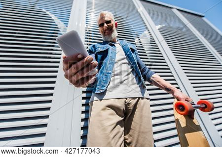 Low Angle View Of Pleased Middle Aged Man In Sunglasses Using Smartphone And Holding Longboard