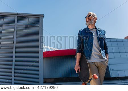 Low Angle View Of Positive Middle Aged Man In Sunglasses Holding Longboard On Urban Street