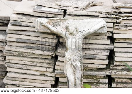 Biblical History: Crucifixion Of Jesus Christ. Ancient Small Stone Statue On The Background Of Old T