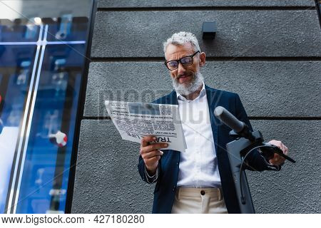 Low Angle View Of Happy Mature Businessman In Blazer Reading Newspaper Near E-scooter