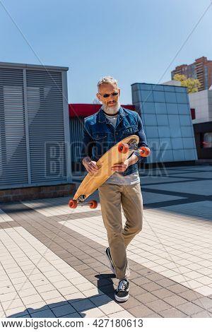 Bearded And Mature Man In Sunglasses Holding Longboard On Urban Street