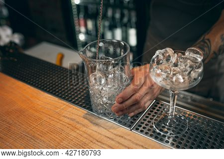 Ice In The Glasses. One Professional Bartender Mixing Cocktails With Long Spoon In Pub Or Cafe. Clos