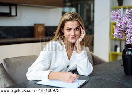 A Young Woman Is Working In Her Kitchen And Is Writing Something In A Notebook. Businesswoman Works