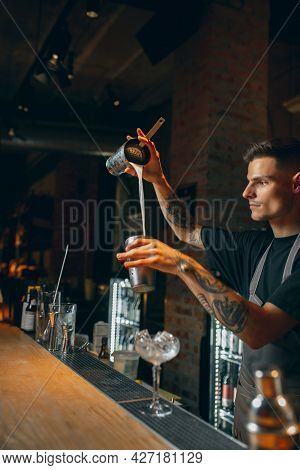 One Professional Bartender Shaking An Alcohol Drink In Cocktail Shaker Enjoying His Job. Side View