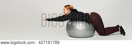 Side View Of Plus Size Sportswoman Training On Fitness Ball On Grey Background, Banner