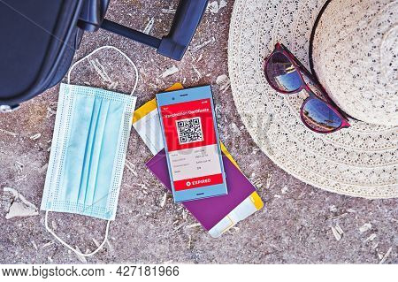 Smartphone Displaying Valid Digital Vaccination Certificate For Covid-19, Suitcase, Summer Hat, Pass