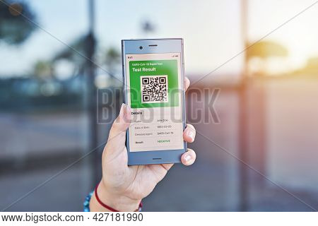 Hand Woman Holds Smartphone Displaying An App Negative Test Result Of Covid-19. Express Pcr Test, Di