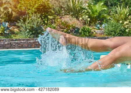 Woman Feet In Pool With Blue Water. Suntanned Legs Splashing In Swimming Pool. Water Splashes From F